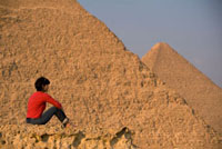 Woman on rocky outcrop looking over Pyramids