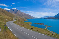 Empty bendy road by lake and Mont Cenis