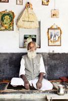 Guru sitting cross legged by wall