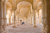 Tourist sitting in columned hallway in the  Amber Fort