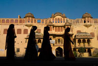 Silhouette of four women in saris walking past old building