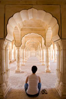 Tourist sitting in columned hallway,Amber Fort
