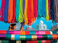 View through bead stall towards woman and Taj Mahal