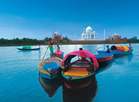 Men on Boats on river in front of the Taj Mahal