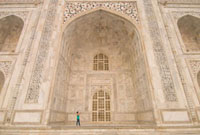 Woman photographing in great arch of the Taj Mahal at dawn