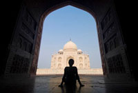 Silhouette of woman in arch admiring the Taj Mahal