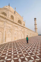 Woman walking beneath the Taj Mahal on tiled ground