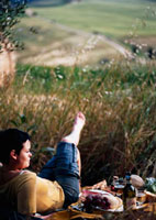 Woman relaxing beside picnic in field