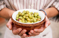 Man holding a bowl of green olives
