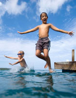 Two children jumping off pier into the ocean