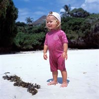 Young blond child standing on beach by seaweed
