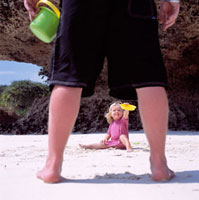 View through father's legs of child playing in the sand