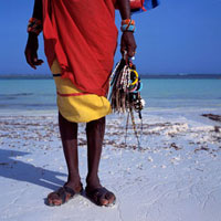 Maasai vendor holding jewelry on the beach,Low Angle View