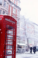 Snow falling on red telephone box in marketplace,