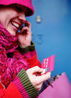 Smiling woman in pink holding credit card while talking on m