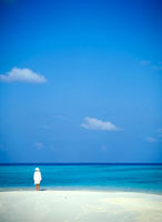 Woman in white standing on edge of tropical beach