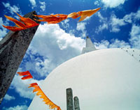 White stupa of Ruwanveliseya Dagoba with orange prayer flags