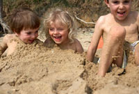 Three kids laughing while being buried in sand on the beach