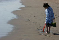 Young girl with bucket and spade playing at sea's edge