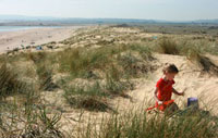 Young girl playing on sand dune with bucket and spade