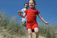 Girls running down sand dunes