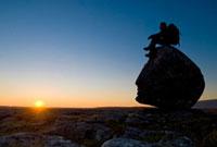 Hiker sitting on head-shaped boulder