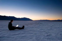 Man using laptop on the salt pans at dawn