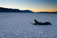 Man lying down using laptop on the salt pans at dawn