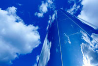 Glass obelisk with blue sky and cloud reflections