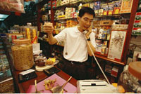 Man Displaying Herbal Medicines In Shop