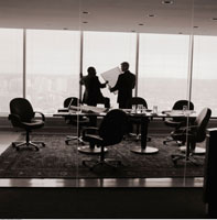 Back View of Businessmen Talking Near Window in Boardroom