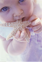 Close-Up of Young Girl Putting Starfish in Mouth