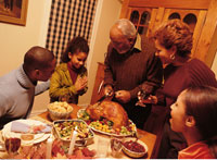 Grandfather Carving Turkey at Thanksgiving Dinner Table