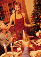 Woman Serving Christmas Dinner To Family at Table
