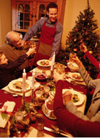 Family Toasting with Wine Glasses At Christmas Dinner Table