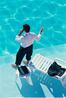 Back View of Businessman Standing In Swimming Pool Using Cel