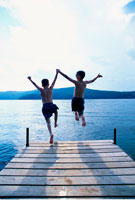 Back View of Boys in Swimwear Jumping into Water from Dock
