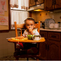 Portrait of Baby Sitting in High Chair with Food on Face