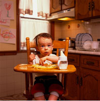 Portrait of Baby Sitting in High Chair with Food