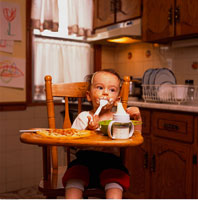 Baby Sitting in High Chair Eating Food