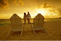 Couple on Beach Walking Toward Adirondack Chairs Paradise Is