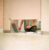Woman Using Laptop in Bathroom Stall
