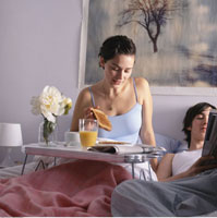 Couple with Breakfast and Newspaper in Bed