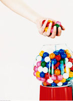 Hand Taking Gumballs out of Gumball Machine