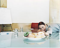 Woman Reaching for Doughnuts in Boardroom