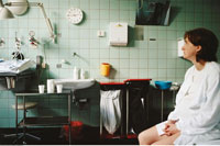 Pregnant Woman Looking at Clock in Hospital Room
