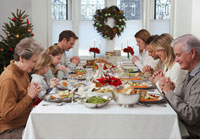 Family Praying at Christmas Dinner