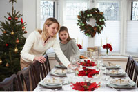 Mother and Daughter Setting the Table for Christmas Dinner