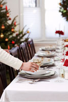 Woman Setting Table for Christmas Dinner