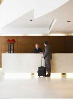 Businessman Talking to Receptionist in Hotel